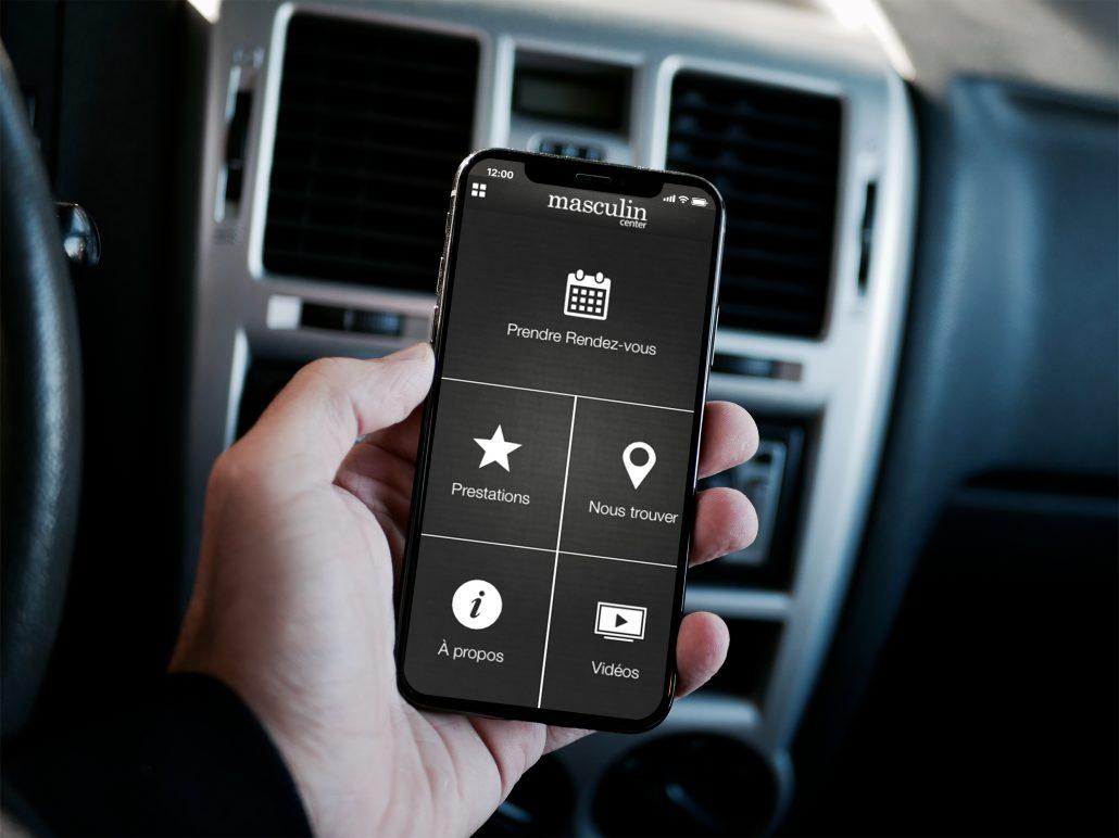 Personne tenant un smartphone dans la main présentant l'application web de masculin center